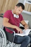 Disabled man in wheelchair reading book Royalty Free Stock Photo