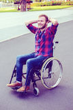 Disabled man in wheelchair on road is smiling Royalty Free Stock Photo