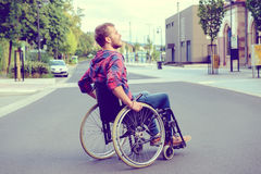Disabled man in wheelchair on road Royalty Free Stock Image