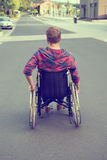 Disabled man in wheelchair on road Stock Photography