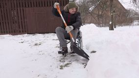Disabled man on wheelchair with snow showel in the yard stock video footage