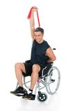 Disabled man on wheelchair stretching with resistance band. Over White Background Royalty Free Stock Photography
