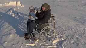 Disabled man on wheelchair talking on phone near bus stop stock footage