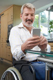 Disabled Man In Wheelchair Texting On Mobile Phone At Home Stock Photo
