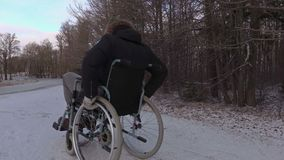 Disabled man on wheelchair try to cross highway. In winter   day stock video footage