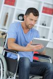 Disabled man in wheelchair using digital tablet at home royalty free stock photos
