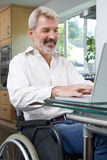 Disabled Man In Wheelchair Using Laptop At Home Stock Photos