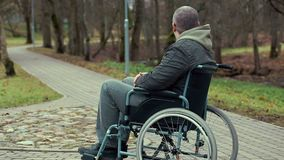 Disabled man in wheelchair waiting for assistance on path in the park. Autumn day stock footage