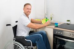 Disabled man on wheelchair washing dishes Stock Photos