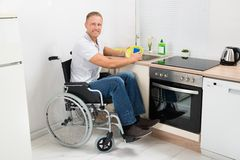 Disabled man on wheelchair washing dishes Royalty Free Stock Photos