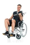 Disabled man on wheelchair working out with dumbbell. Smiling Disabled Man On Wheelchair Working Out With Dumbbell Over White Background Royalty Free Stock Photography