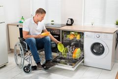 Disabled man working in kitchen Royalty Free Stock Image