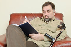 Disabled man writing agenda Stock Image