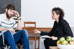 Disabled man with young psychotherapist. Disabled men talking with young psychotherapist about his mental health Stock Images