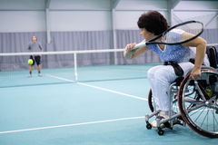 Disabled mature woman on wheelchair playing tennis on tennis court.  Royalty Free Stock Photography