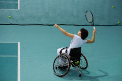 Disabled mature woman on wheelchair playing tennis on tennis court Stock Images