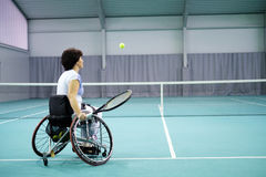 Disabled mature woman on wheelchair playing tennis on tennis court. Stock Photos