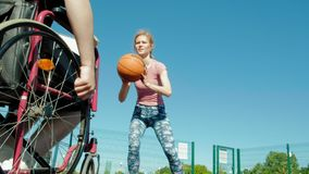 Disabled man plays basketball from his wheelchair With a woman, On open air, Make an effort when playing. Disabled men plays basketball from his wheelchair With royalty free stock photography