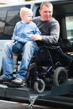 Disabled Men with son on Wheelchair Lift royalty free stock images