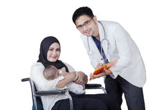 Disabled mother and doctor look at camera Royalty Free Stock Photography