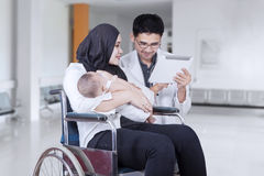 Disabled mother and doctor with tablet Stock Photography