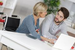 Disabled mother and son consider new software on laptop. Adult royalty free stock photography