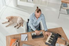 Disabled musician working with mpc pads. High angle view of disabled musician on wheelchair working with mpc pads stock photo