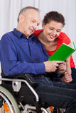 Disabled and a nurse reading a book together Stock Images