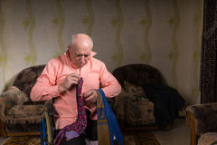Disabled old man is choosing a tie Stock Photography
