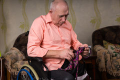 Disabled old man is focused on a tie Royalty Free Stock Photography