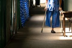 Disabled Old Man Walking in the Small Walk Path in the Hospital royalty free stock image