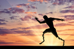 Disabled paralympians with two prosthetic running. Disabled paralympic with two prosthetic running on sunset background. Concept sport and willpower Royalty Free Stock Photography