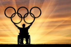 Disabled Paralympic keep olympic rings sunset. Paralympic wheelchair raised his hands to keep the Olympic rings and the sunset. Sports and willpower Concept Royalty Free Stock Photos