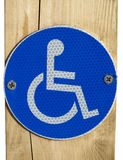 A Disabled Parking Sign. A reflective disabled parking sign on wooden post stock photos