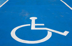 Disabled parking sign. On blue background Royalty Free Stock Photo