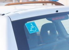 Disabled parking sticker tag on car. Blue disabled parking sticker tag on rear windshield of car Royalty Free Stock Photo