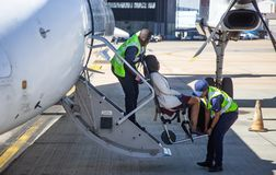 Disabled passenger being helped to board aircraft stock images