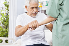 Disabled Patient Holding Hand Of Nurse In Rehab Center. Disabled senior patient holding hand of female nurse in rehab center Royalty Free Stock Photos