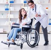 Disabled patient on wheelchair visiting doctor for regular check royalty free stock images