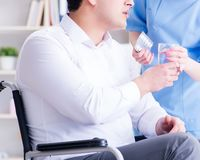 Disabled patient on wheelchair visiting doctor for regular check royalty free stock photos