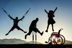 Disabled people jumping. Silhouettes of disabled people jumping on the hilltop at sunset Stock Photos