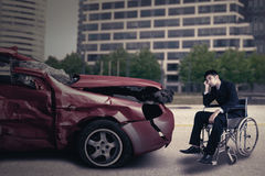 Disabled person with damaged car looks sad Stock Images