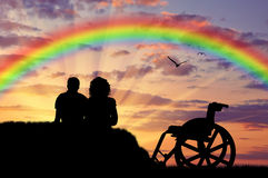 Disabled person with a nurse, happy rainbow. Disabled concept. A disabled person with a nurse, happy rainbow and sea sunset Stock Photography