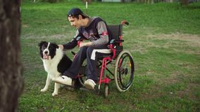 A disabled person plays with a dog, canitis therapy, disability treatment through training with a dog, Man in a