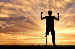 Disabled person with prosthetic leg and to pick up hands sunset. Disabled person with prosthetic leg standing on hill and raise hands up on sunset. Concept Royalty Free Stock Images