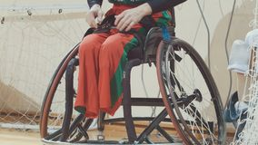 Disabled person with protes of legs transplanted to wheelchair for sportive training. Close up Stock Image