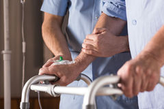 Disabled person walking with assistance Stock Image