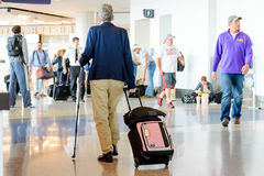 Disabled person walking with stick and luggage in airport Stock Photos