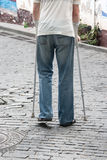 The disabled person walks in park on crutches Royalty Free Stock Image