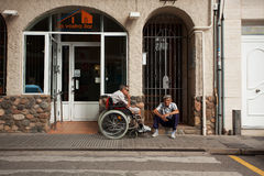 Disabled person in a wheelchair on a city street Royalty Free Stock Images